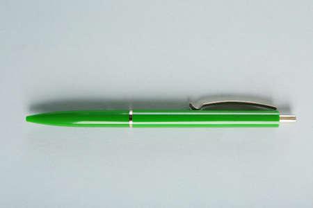Blank green ballpoint pen on grey  background