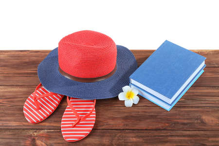 Vacation concept. Book, hat and flip-flops on wooden table