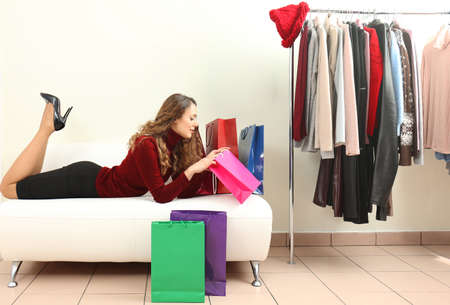 Beautiful young woman with paper bags lying on couch in modern shop Standard-Bild