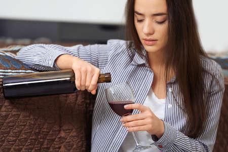 Depressieve vrouw het drinken van wijn binnenshuis