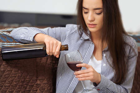 Depressed woman drinking wine indoors