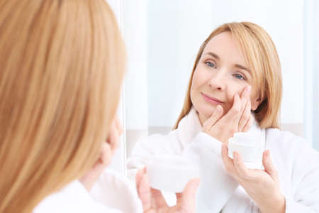 Happy senior woman applying anti-aging cream near mirror Banco de Imagens