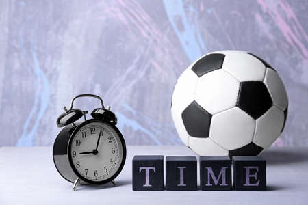 Cubes with alarm clock and soccer ball on color background. Time concept