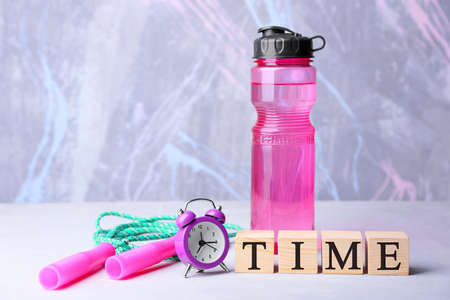 Cubes, alarm clock and jumping rope with bottle on color background. Time concept