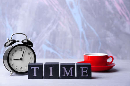 Cubes with alarm clock and cup on wooden table. Time concept