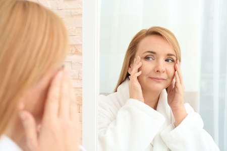 Happy senior woman applying anti-aging cream near mirror Foto de archivo