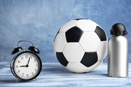 Alarm clock and soccer ball with bottle on color background