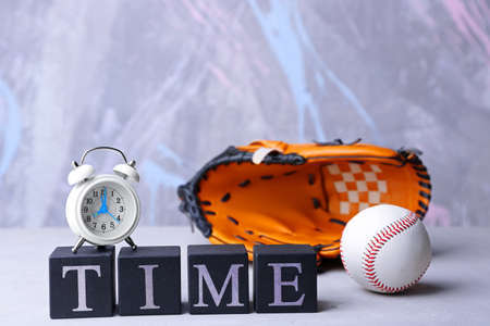 Cubes with alarm clock and baseball glove on color background. Time concept