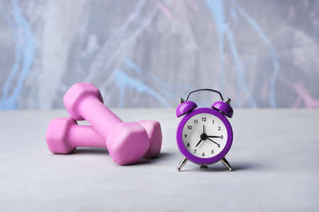 Alarm clock and dumbbells on color background