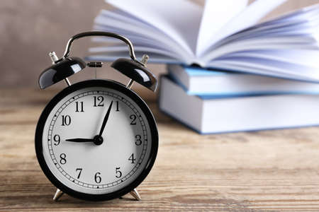 Alarm clock and stack of books on wooden table