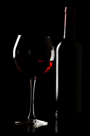 Glass of wine with bottle in darkness Stock Photo