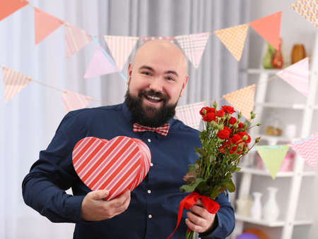 Funny fat man with giftbox and flowers at birthday party