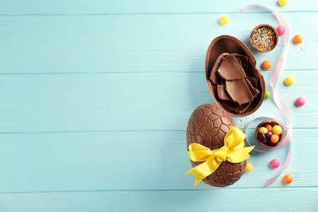 Wielkanocna kompozycja z czekoladowymi jajkami na kolorowym drewnianym tle, miejsca na tekst Zdjęcie Seryjne
