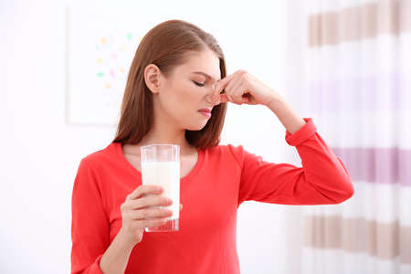 Young woman refusing to drink milk Stock Photo