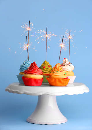 Cupcakes with sparklers on color background