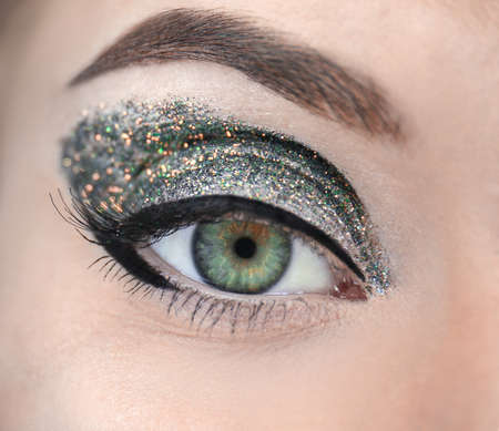 Female eye with fancy glitter makeup, closeup