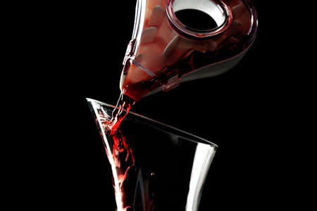 Pouring red wine into decanter on dark background Stock Photo