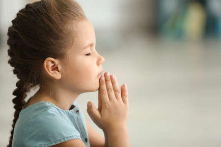 Cute little girl praying at home