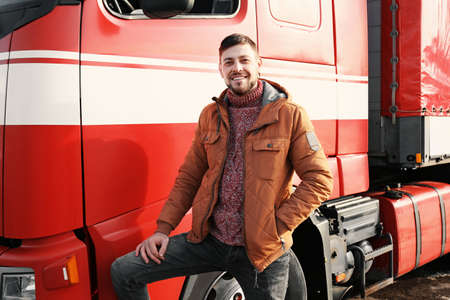 Handsome driver near big modern truck outdoors Stock Photo