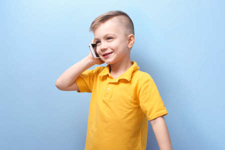 Cute little boy talking by mobile phone on color background Stock Photo