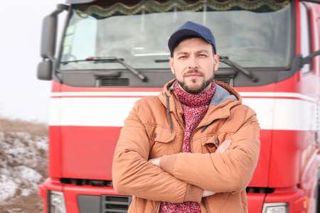 Handsome driver near big modern truck outdoors