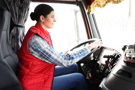 Joven conductora sentada en la cabina del gran camión moderno% 00