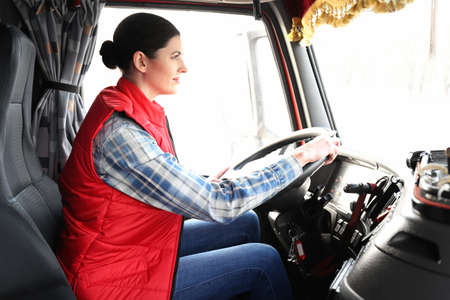 Young female driver sitting in cabin of big modern truck Stok Fotoğraf