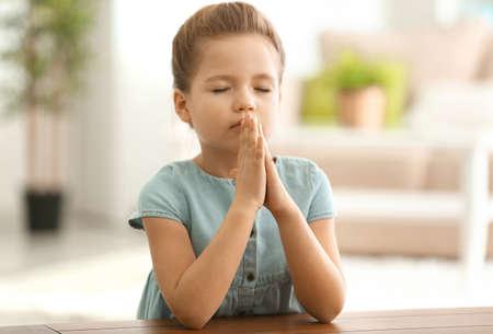 Schattig klein meisje dat thuis% 00 bidt Stockfoto