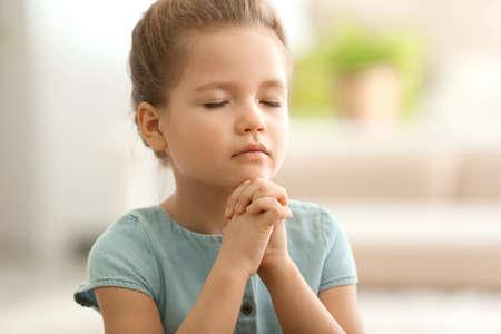 家で祈るかわいい女の子 写真素材