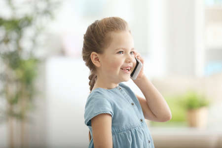 Cute little girl talking by mobile phone at home Stock Photo