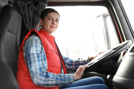 Young female driver sitting in cabin of big modern truck 스톡 콘텐츠