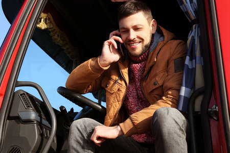 Driver talking by mobile phone while sitting in cabin of big modern truck Stock Photo