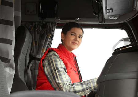 Female driver in cabin of big modern truck