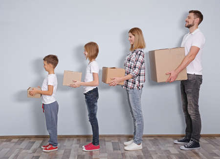 House move concept. Family with cardboard boxes standing in a row at home