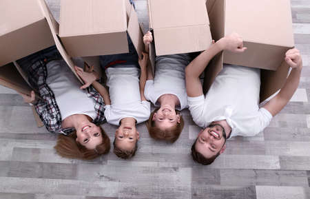 Family with cardboard boxes lying on floor