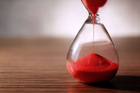 Crystal hourglass with red sand on wooden table