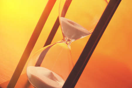 Black hourglass with white sand on color background