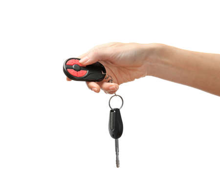 Female hand holding car keys on white background