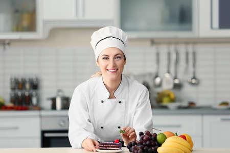Vrouwelijke chef-kok die cake in keuken verfraait