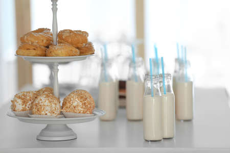 Table with bottles of milk and dessert stand Stock Photo
