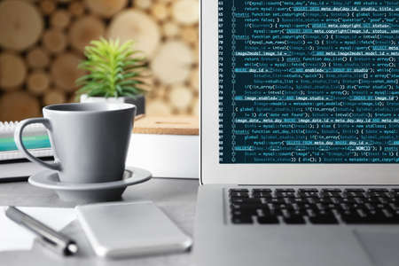 Laptop of programmer with script code on display Stock Photo