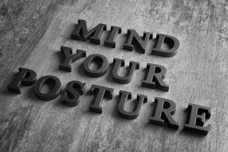 Black letters forming phrase MIND YOUR POSTURE on grey backgroud