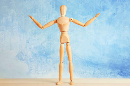 Wooden mannequin with raised hands on table, light background