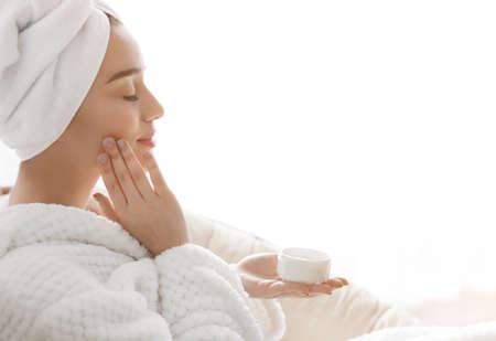 Belle jeune femme appliquant la crème sur la peau dans le salon spa