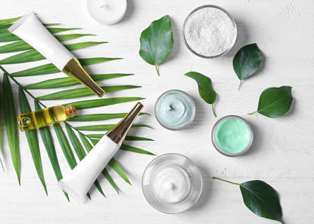 Natural cosmetics and leaves on wooden table