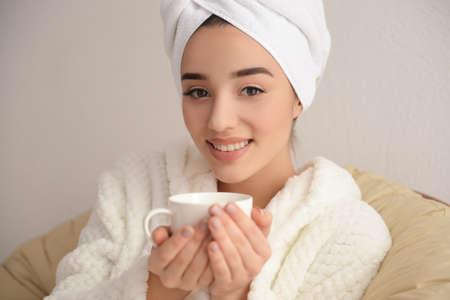 Beautiful young woman drinking coffee in spa salon