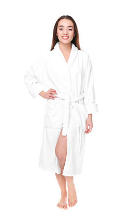 Beautiful young woman in bathrobe on white background