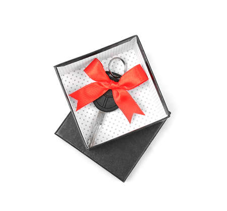 Gift box with car key isolated on white