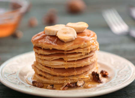 Tasty pancakes with banana, nuts and honey on plate
