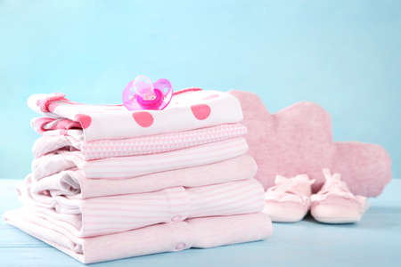 Pile of baby clothes on blue wooden background